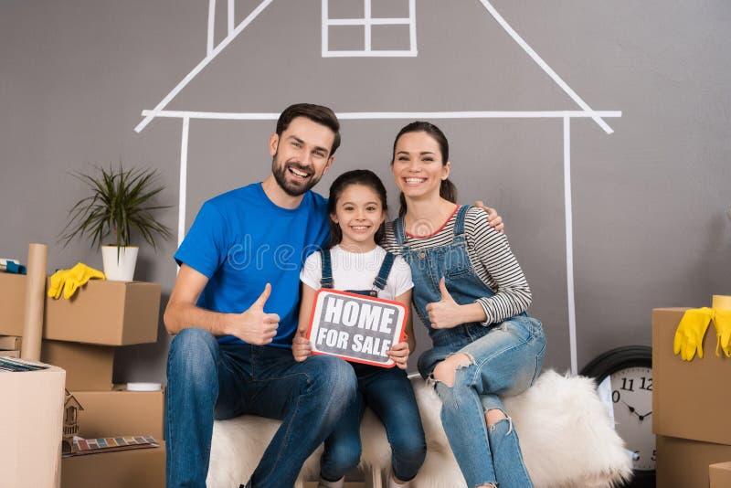 Concepto 6 de las propiedades inmobiliarias Concepto de venta de casa La familia feliz vende la casa foto de archivo libre de regalías