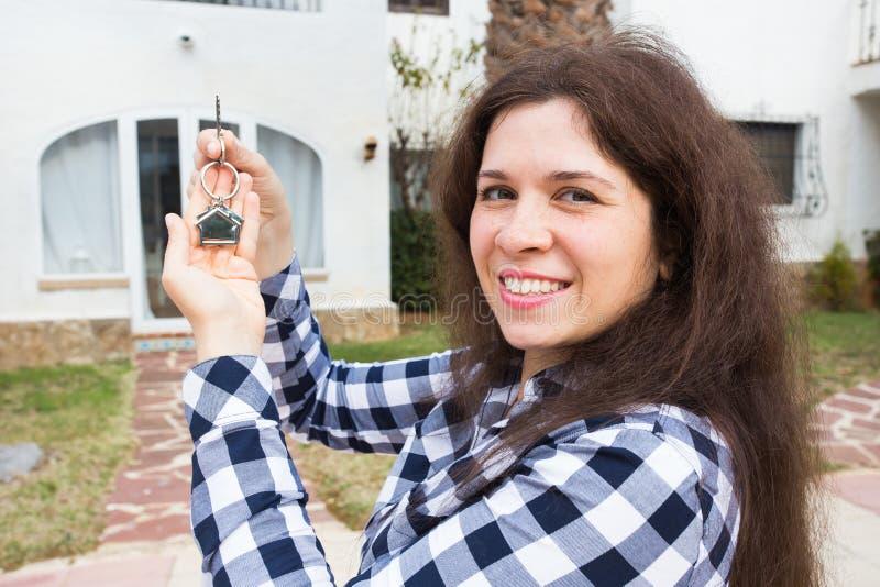 Concepto de las propiedades inmobiliarias y de la propiedad Propiedad feliz Mujer joven atractiva que lleva a cabo llaves mientra fotos de archivo libres de regalías