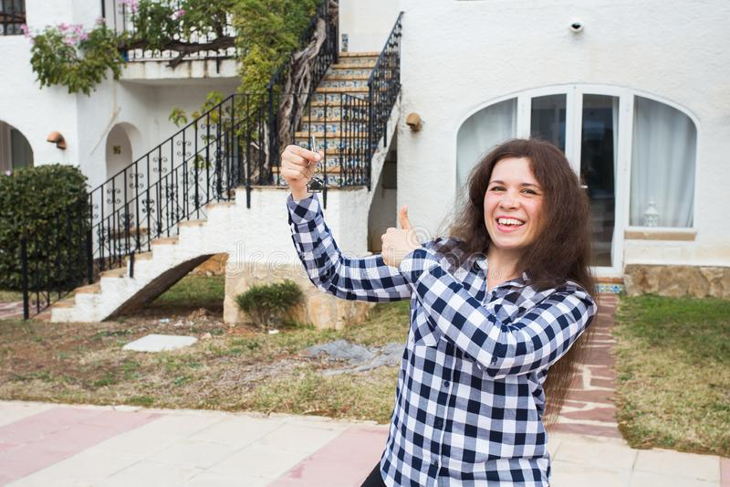 Concepto de las propiedades inmobiliarias y de la propiedad Propiedad feliz Mujer joven atractiva que lleva a cabo llaves mientra foto de archivo libre de regalías