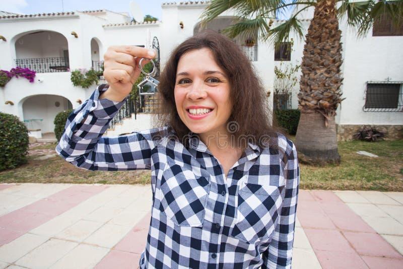 Concepto de las propiedades inmobiliarias y de la propiedad Propiedad feliz Mujer joven atractiva que lleva a cabo llaves mientra imagen de archivo libre de regalías