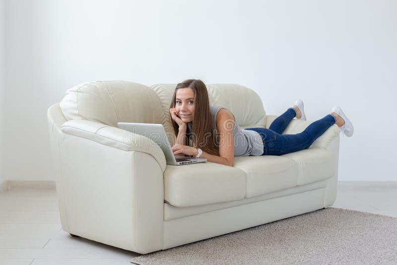 Concepto de las tecnologías, independiente y de la gente - mujer bastante joven que miente en el sofá con el ordenador portátil foto de archivo