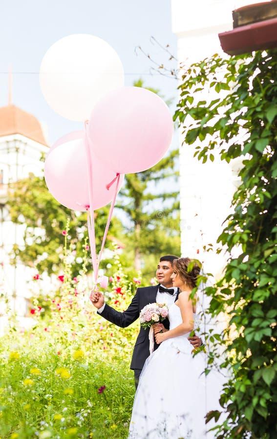 Concepto de las vacaciones de verano, de la celebración y de la boda - par con los globos coloridos fotos de archivo libres de regalías