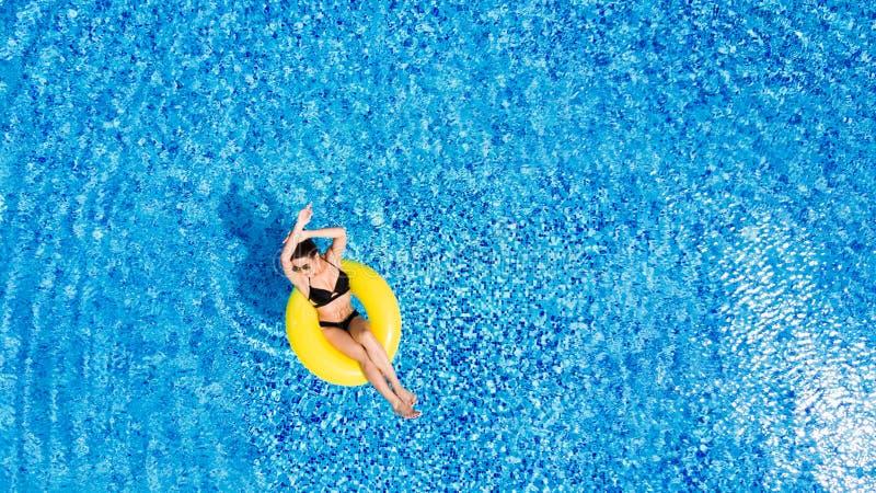 Concepto de las vacaciones Opinión superior la mujer joven delgada en bikini en el anillo inflable del aire amarillo en la piscin foto de archivo