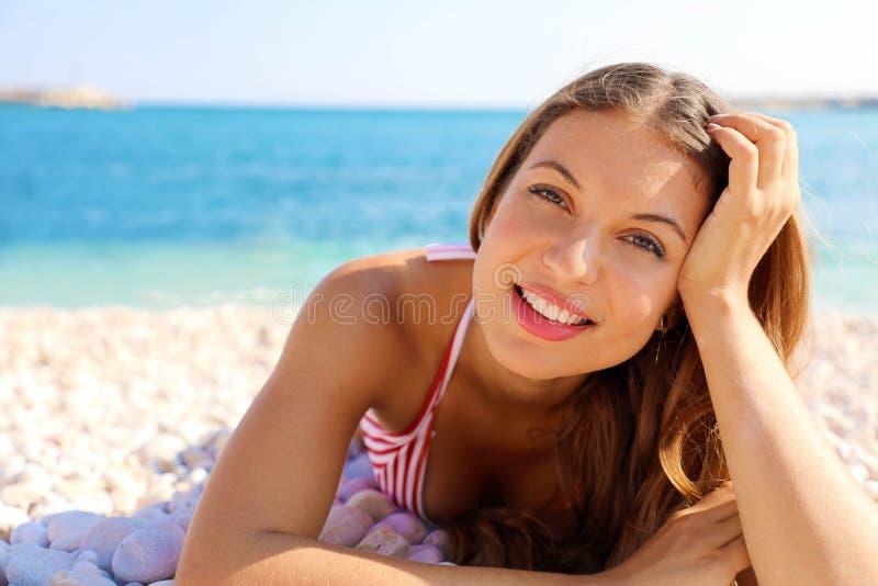 Concepto de las vacaciones de verano El goce sonriente joven de la mujer relaja la mentira en la playa que mira la cámara imagen de archivo libre de regalías