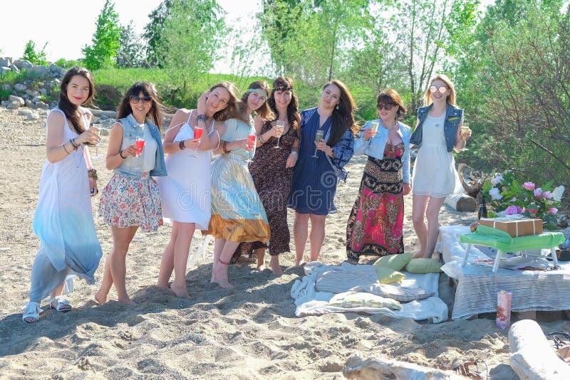 Concepto de las vacaciones de verano - el grupo de mujeres jovenes sonrientes se está basando sobre la costa fotografía de archivo