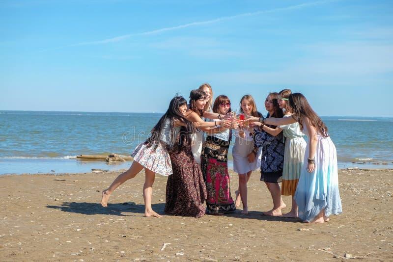 Concepto de las vacaciones de verano - el grupo de mujeres jovenes sonrientes se está basando sobre la costa imagen de archivo libre de regalías