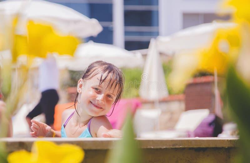 Concepto de las vacaciones de verano Muchacha feliz del pequeño niño que juega al aire libre en piscina de agua imagen de archivo