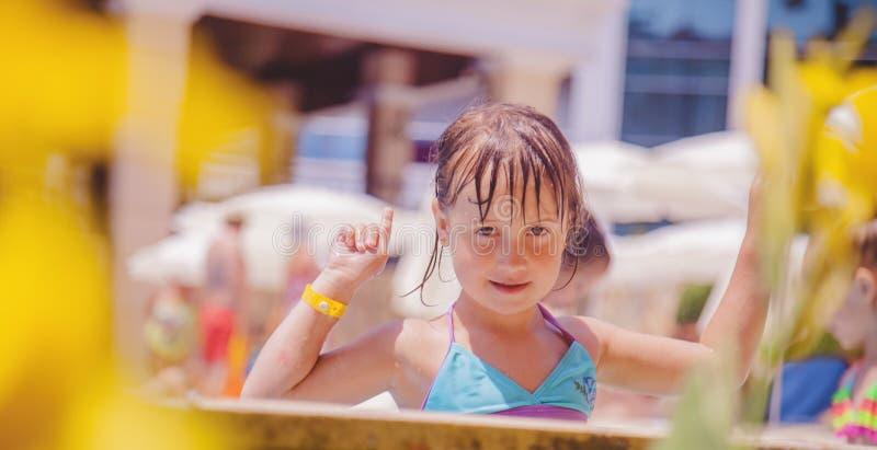Concepto de las vacaciones de verano Muchacha feliz del pequeño niño que juega en agua en aire libre en la piscina fotos de archivo