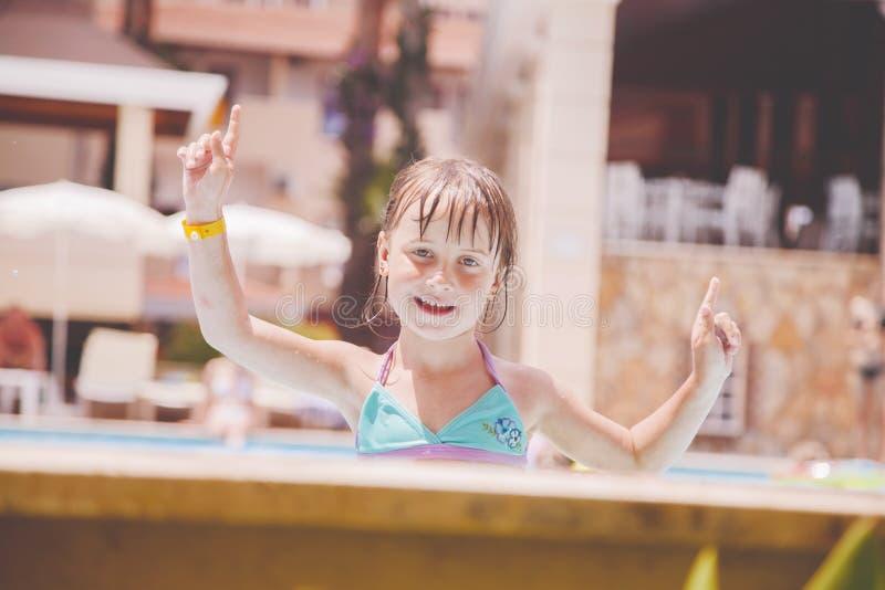 Concepto de las vacaciones de verano Niña feliz que juega en agua en aire libre en la piscina imagen de archivo