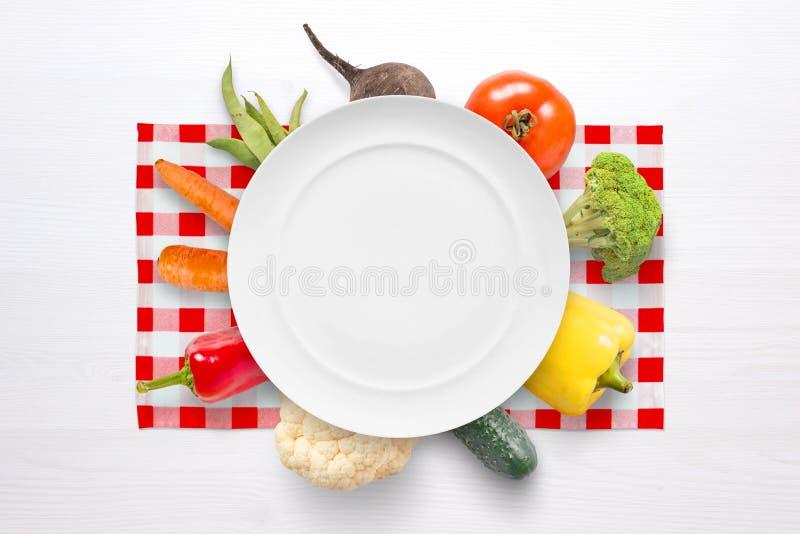 Concepto de las verduras del vegano con la placa y las verduras vacías en el mantel blanco rojo imagen de archivo
