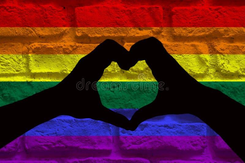 Concepto de LGBT, silueta de dos manos que hacen una forma del corazón junta, en una pared de ladrillo con el modelo de la bander ilustración del vector