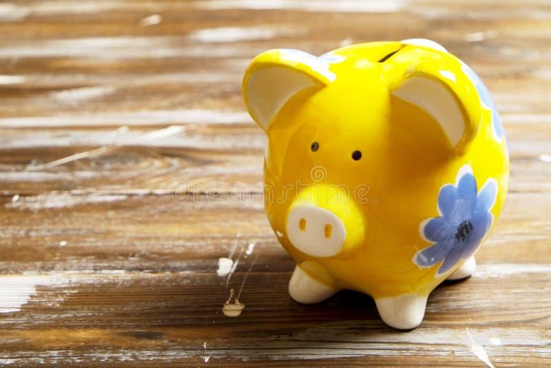 Concepto de los ahorros Hucha y dinero en fondo de madera oscuro foto de archivo libre de regalías