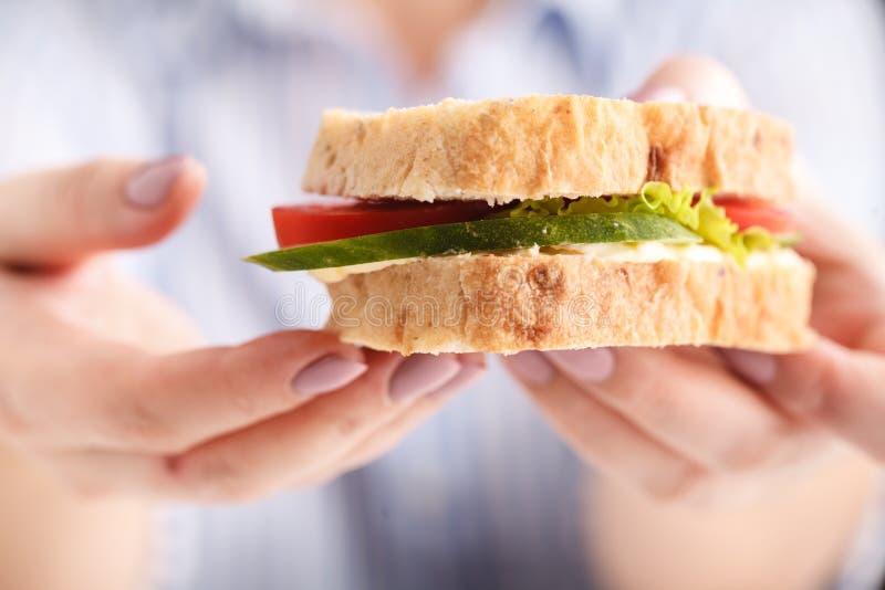 Concepto de los alimentos de preparación rápida Bocadillo malsano sabroso de la hamburguesa en las manos colgadas foto de archivo libre de regalías