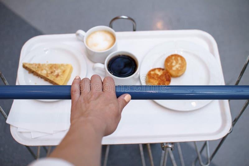 Concepto de los alimentos de preparaci?n r?pida En marco la mano lleva un carro, una bandeja de café, la torta y los pasteles de  imagen de archivo libre de regalías