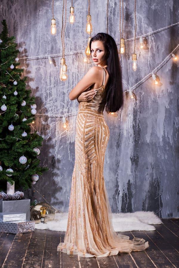 Concepto de los días de fiesta, de la celebración y de la gente - mujer morena joven en vestido largo de oro elegante sobre fondo fotos de archivo libres de regalías