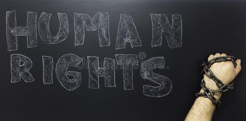 Concepto de los derechos humanos: hombre encadenado contra el texto: Día de los derechos humanos escrito en la pizarra fotos de archivo libres de regalías