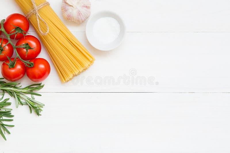Concepto de los ingredientes de los espaguetis en el fondo blanco, visión superior imagen de archivo