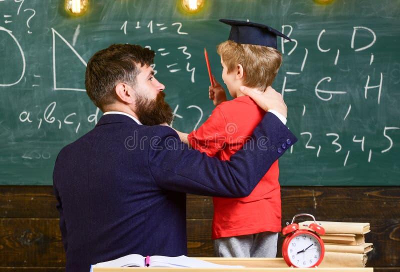 Concepto de los mejores amigos El profesor con la barba, padre abraza al pequeño hijo en sala de clase mientras que discute, piza imagen de archivo