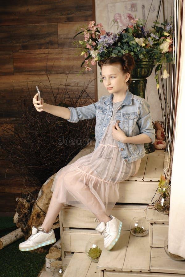 Concepto de los niños, de la tecnología y de la comunicación - muchacha sonriente que manda un SMS en smartphone y hogar de menti imagen de archivo