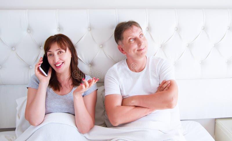 Concepto de los problemas de la relación - un par de mediana edad que miente en cama por la mañana una mujer que sostiene un smar fotos de archivo