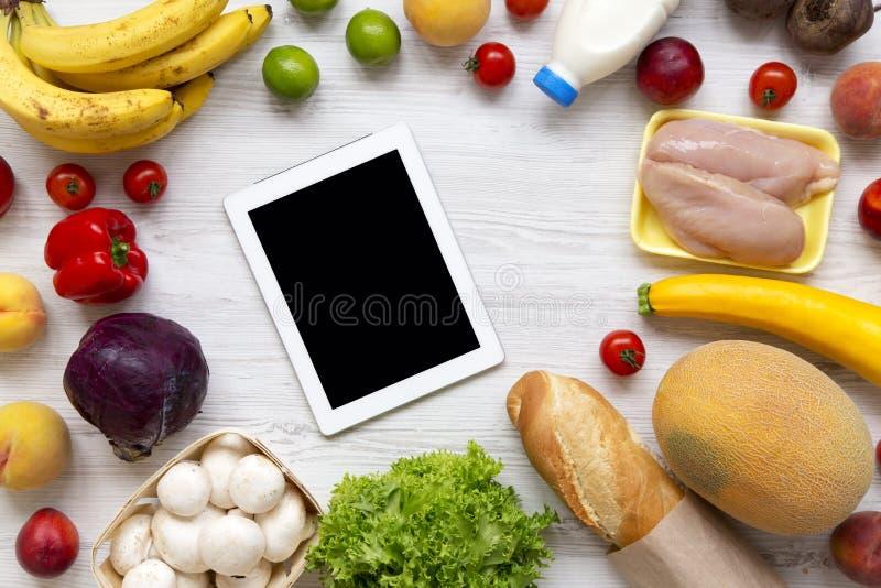 Concepto de los ultramarinos de las compras Composición de la diversa comida sana con la tableta en la tabla de madera blanca Coc imagenes de archivo