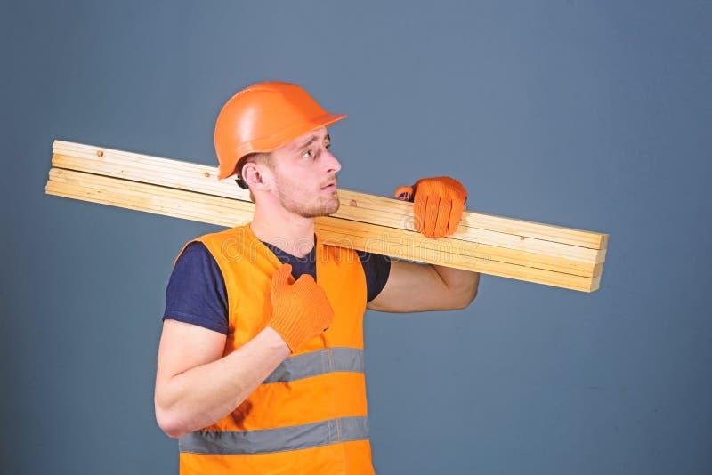 Concepto de madera de los materiales El carpintero, carpintero, constructor fuerte en cara seria lleva el haz de madera en hombro fotos de archivo libres de regalías