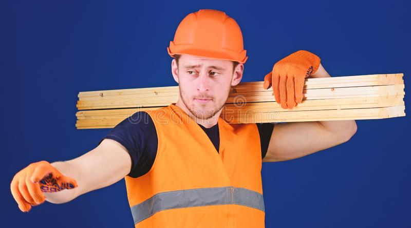 Concepto de madera de los materiales Hombre en la dirección punteaguda del casco, del casco y de los guantes protectores, fondo a fotos de archivo libres de regalías