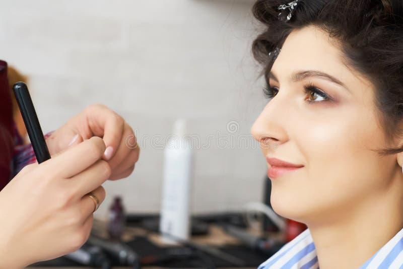 Concepto de moda y de belleza La morenita hermosa con el pelo enorme se preparó para el trabajo de un estilista imagenes de archivo