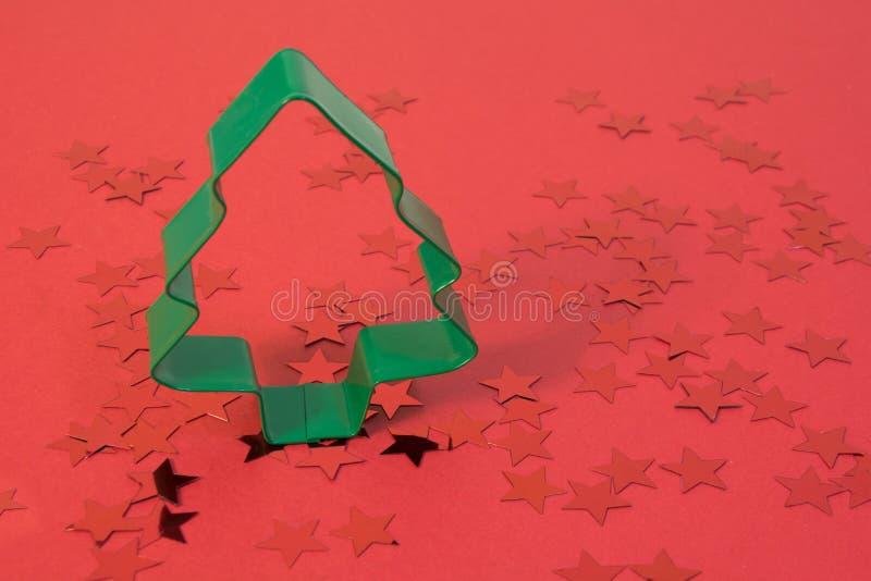 Concepto de Navidad Cortador de la galleta de la Navidad como spruce en fondo rojo con las estrellas brillantes Tarjeta del día d fotografía de archivo libre de regalías