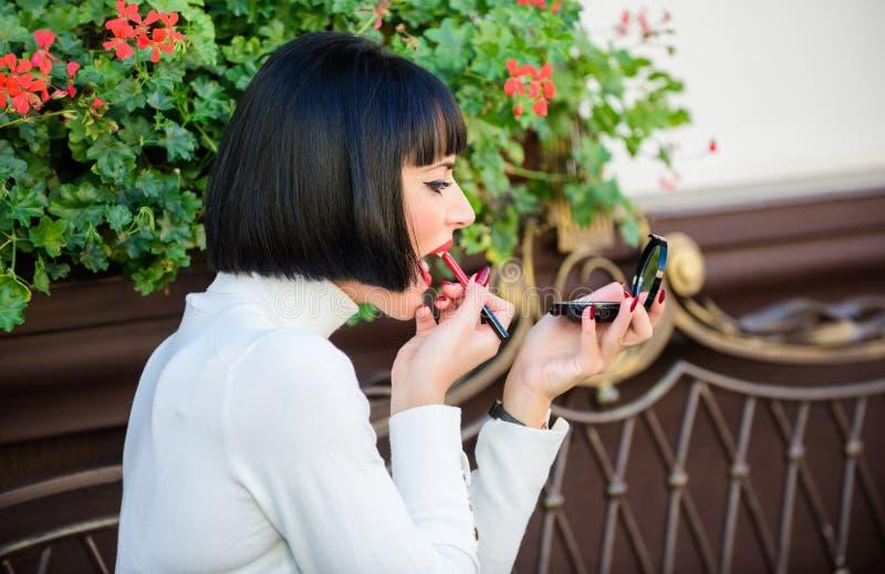 Concepto de niña de los secretos Mujer que hace maquillaje con el espejo del bolsillo Compruebe si todo es justo antes de fecha m fotos de archivo libres de regalías