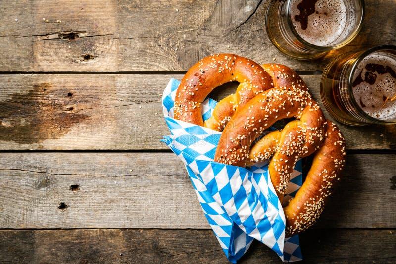 Concepto de Oktoberfest - pretzeles y cerveza en fondo de madera rústico imagen de archivo