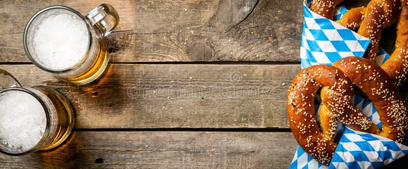 Concepto de Oktoberfest - pretzeles y cerveza en fondo de madera rústico foto de archivo