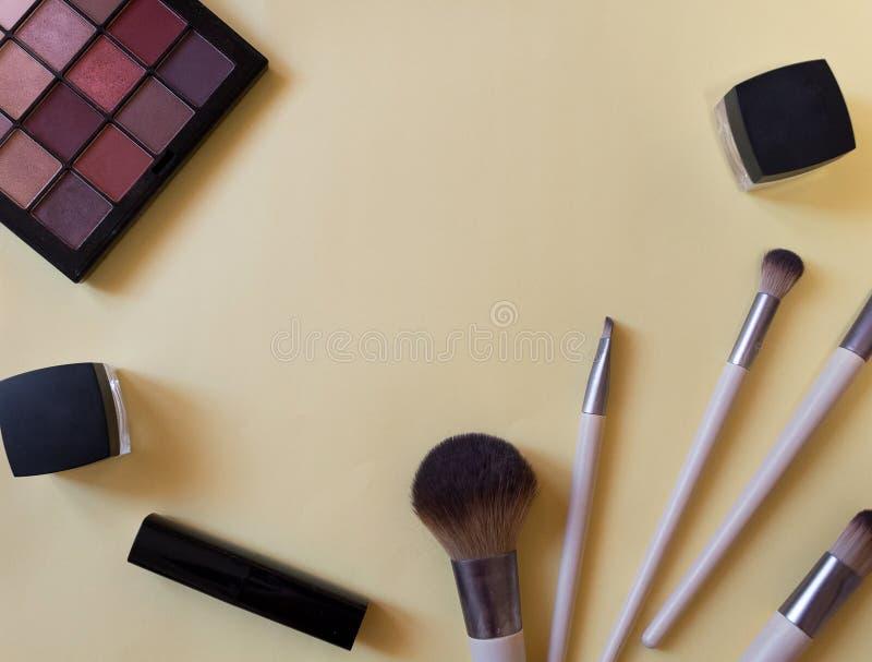 Concepto de opinión superior de los tubos cosméticos y de los envases poner crema sobre fondo rosado Lápiz labial, cepillo, palet imágenes de archivo libres de regalías