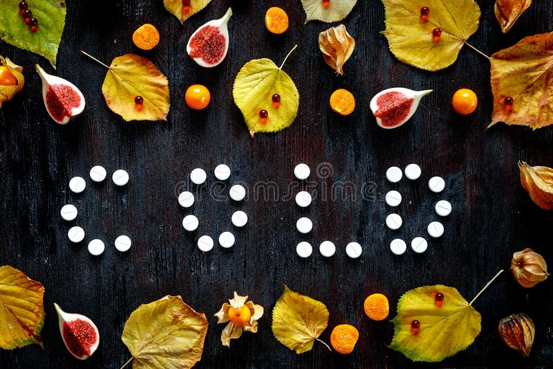 Concepto de otoño frío - píldoras, hojas en la madera oscura imagen de archivo