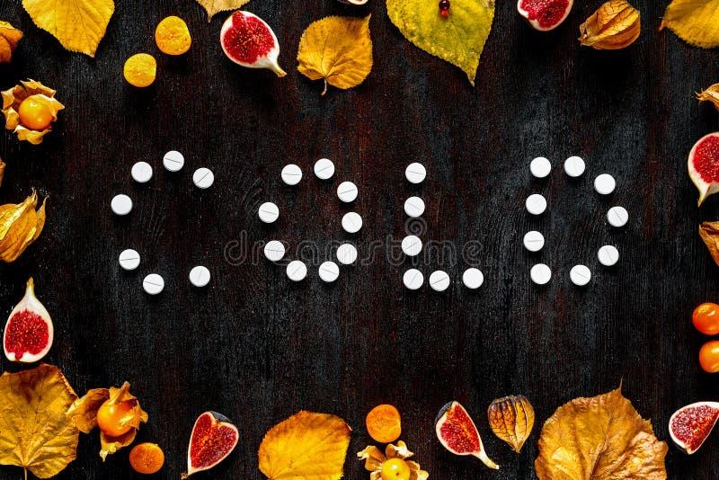 Concepto de otoño frío - píldoras, hojas en la madera oscura imagen de archivo libre de regalías