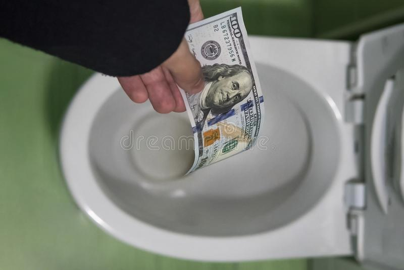 Concepto de pérdida inconsciente de dinero, pérdida, basura inútil, costes grandes del agua, limpiando cientos dólares con un cho imagenes de archivo