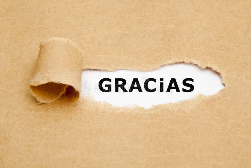 Concepto de papel rasgado Gracias español de la palabra fotografía de archivo libre de regalías