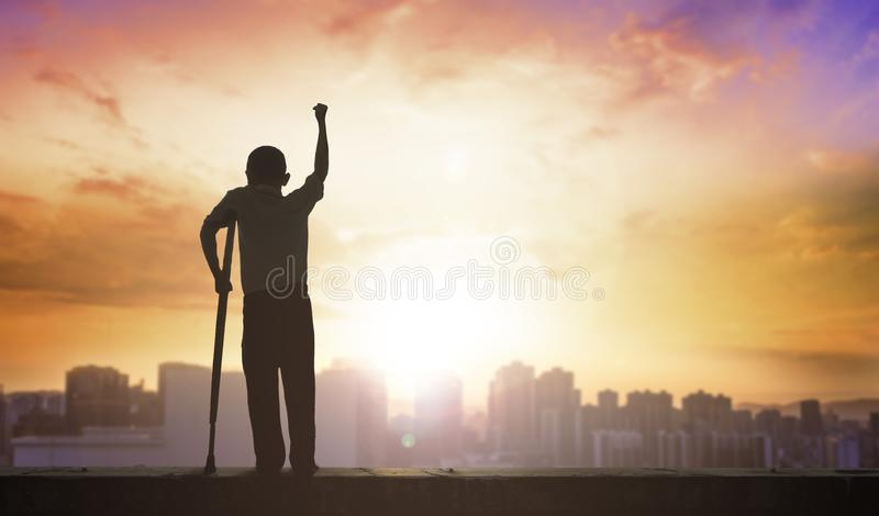 Concepto de Paralympic: persona discapacitada con la silueta de las muletas en el fondo de la puesta del sol, día internacional d fotos de archivo