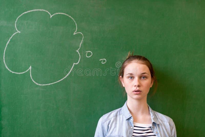 Concepto de pensamiento de la pizarra del estudiante Muchacha pensativa que mira la burbuja del pensamiento en fondo de la pizarr fotografía de archivo libre de regalías