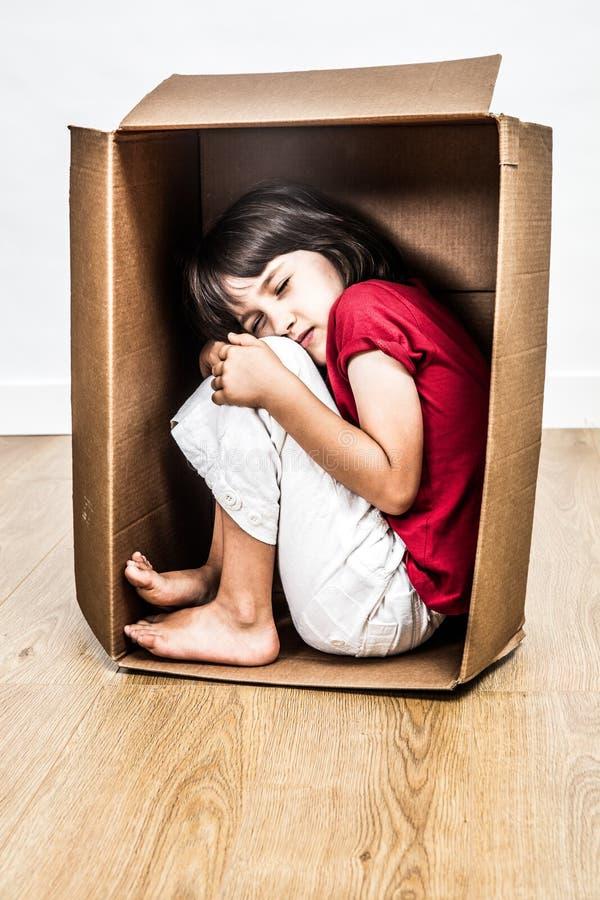 Concepto de pequeño niño para arriba durmiente encrespado hunched en caja imagen de archivo libre de regalías