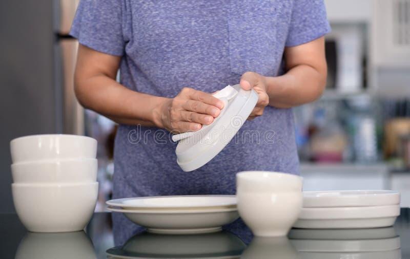 Concepto de producto de limpieza de la mujer que limpia el limpiador del dishware en el hogar a imagen de archivo