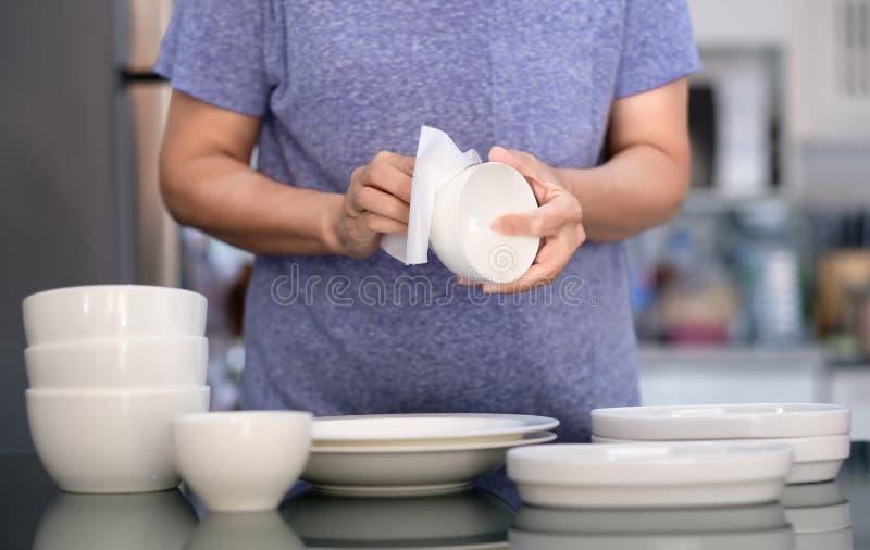 Concepto de producto de limpieza de la mujer que limpia el limpiador del dishware en el hogar a imagen de archivo libre de regalías