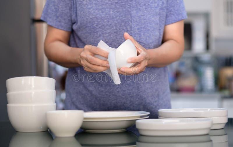Concepto de producto de limpieza de la mujer que limpia el limpiador del dishware en el hogar a foto de archivo libre de regalías