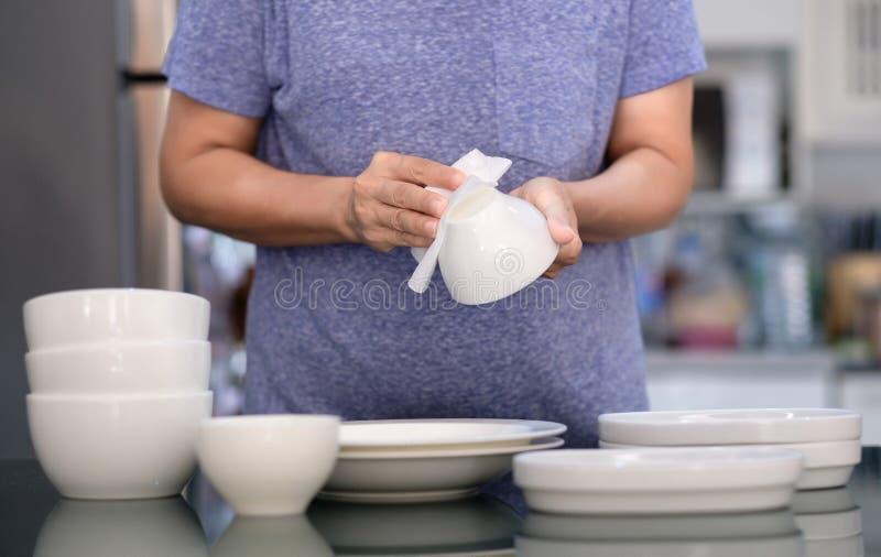 Concepto de producto de limpieza de la mujer que limpia el limpiador del dishware en el hogar a fotografía de archivo