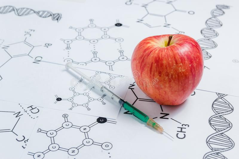 Concepto de productos No-naturales, Gmo Jeringuilla y rojo Apple en el fondo blanco con fórmula química, foto de archivo libre de regalías