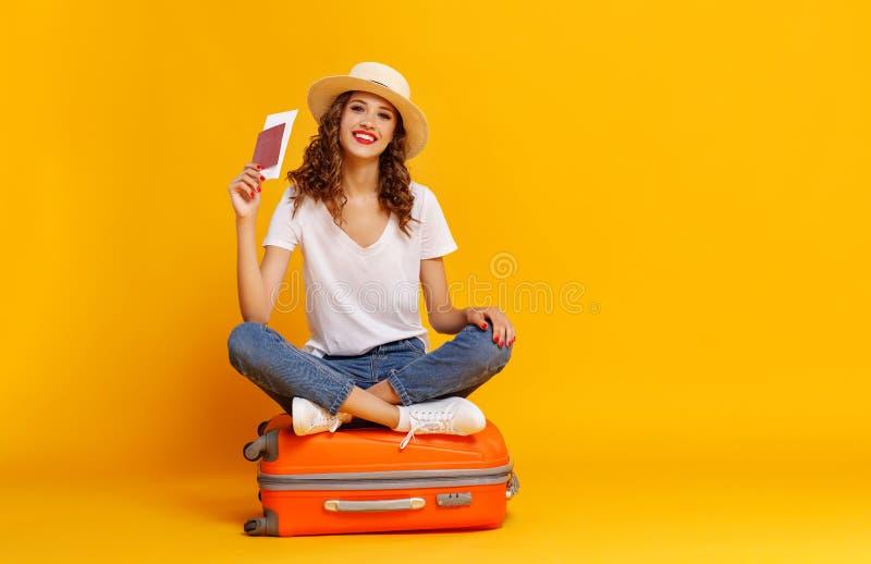 Concepto de recorrido muchacha feliz de la mujer con la maleta y pasaporte en fondo amarillo imagenes de archivo