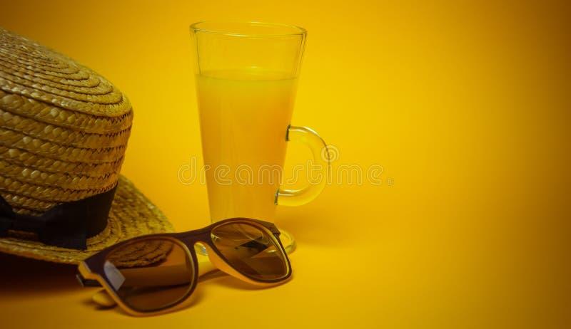 Concepto de relajación y de sed en la playa un vidrio de limonada en un fondo amarillo con gafas de sol y un sombrero de paja tap imágenes de archivo libres de regalías