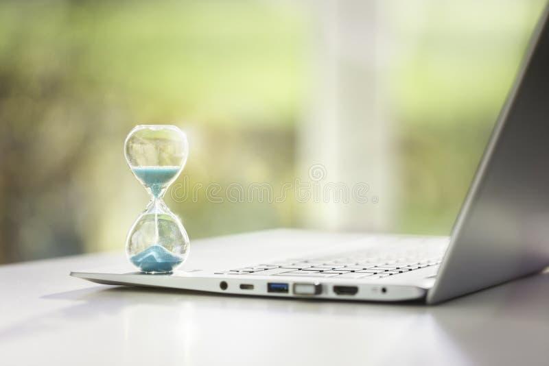 Concepto de reloj de arena en computadora portátil para la administración del tiempo fotografía de archivo