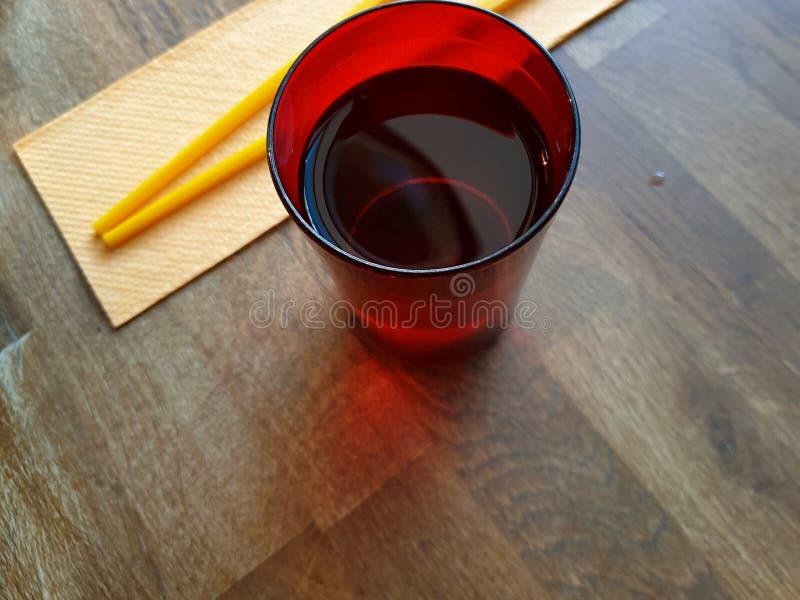 Concepto de restaurante asiático Opinión de sobremesa con los palillos coloridos en una servilleta y una taza brillante del agua  fotos de archivo libres de regalías