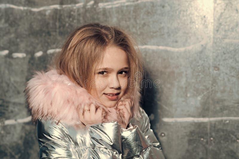 Concepto de Skincare Muchacha en abrigo de invierno con la capilla de la piel, moda Pequeño niño con el pelo rubio, el peinado y  fotos de archivo